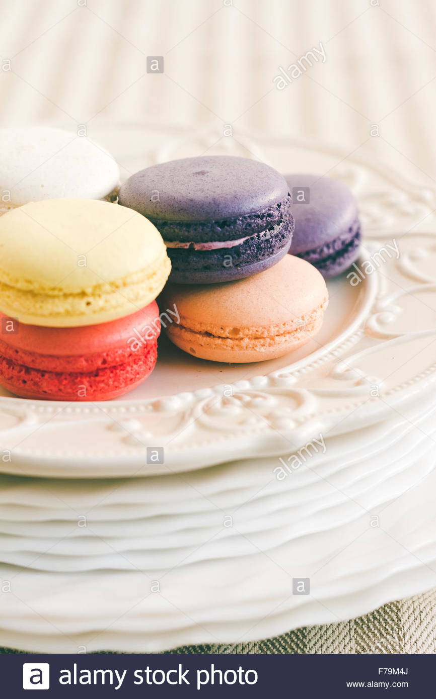Different coloured macarons on white retro plate. Selective Focus - Stock Image