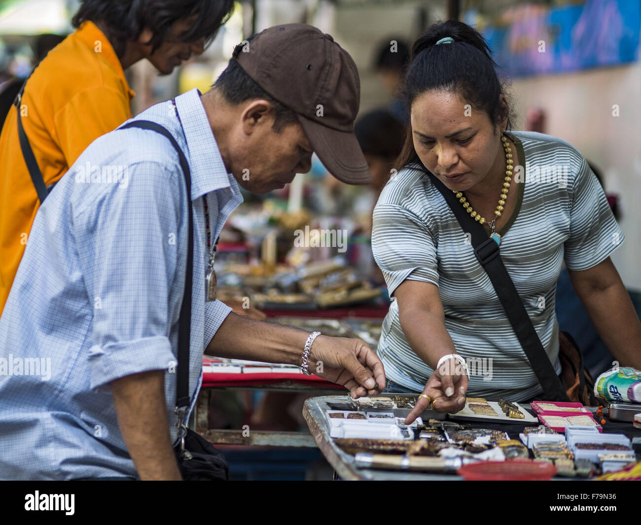 Bangkok, Bangkok, Thailand. 27th Nov, 2015. An amulet vendor points out an amulet to a potential customer at her - Stock Image