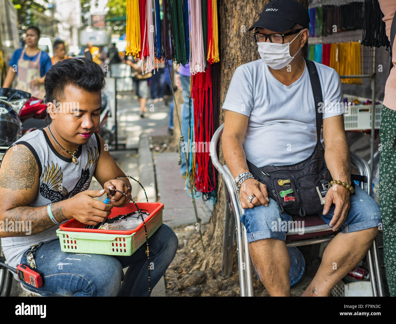 Bangkok, Bangkok, Thailand. 27th Nov, 2015. A street vendor puts together an amulet in his market stall while he - Stock Image