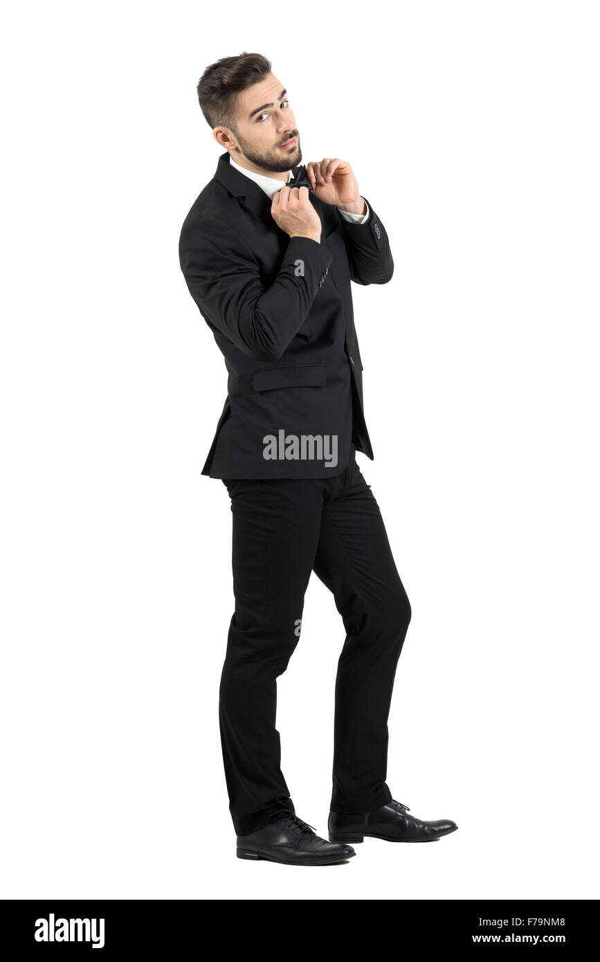 Side view of cool elegant young male model adjusting bow tie looking at camera. Full body length portrait isolated - Stock Image