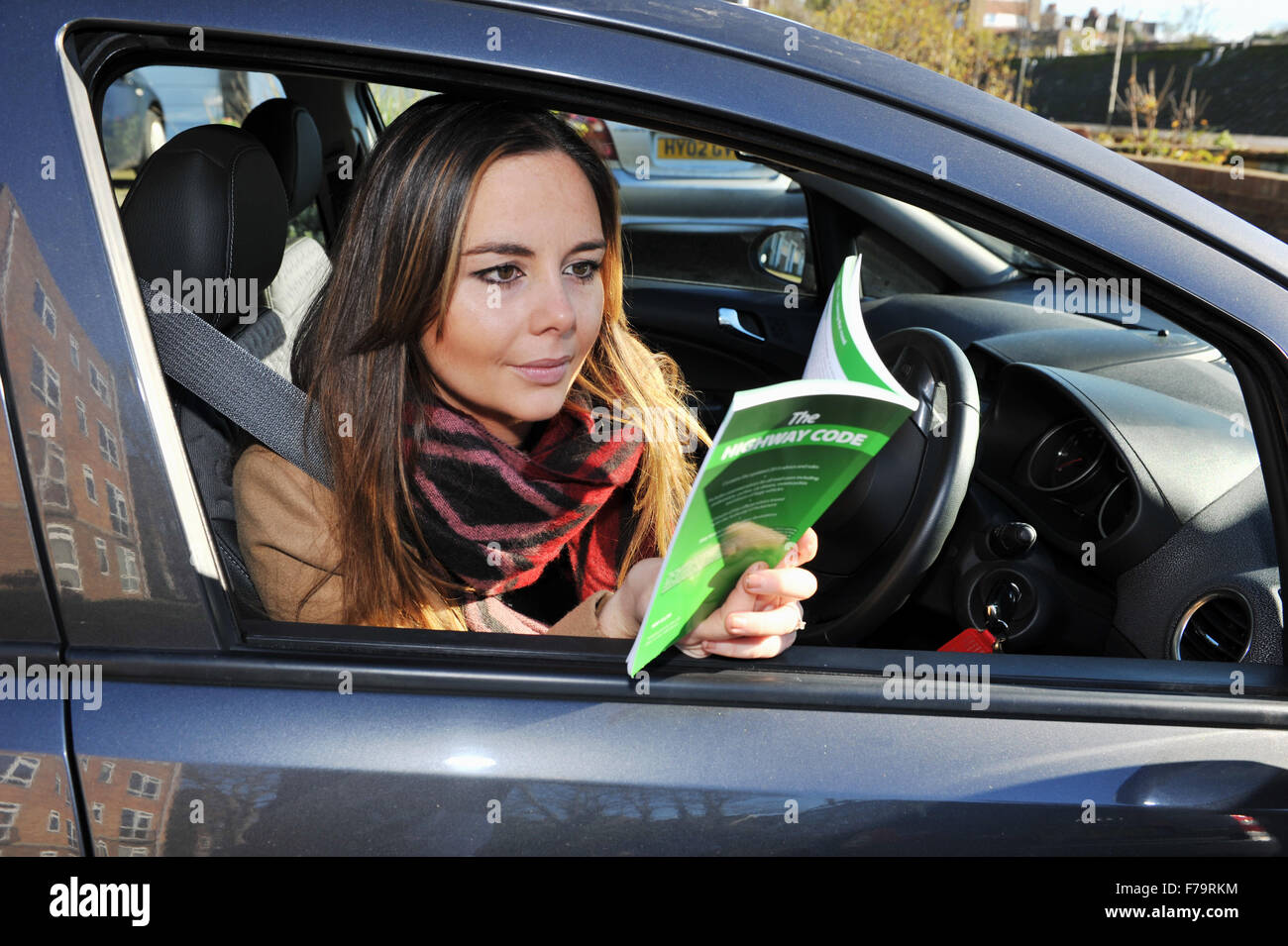 Young female driver with the 2015 edition of the Highway Code UK - Stock Image