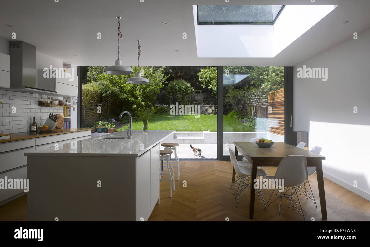 Dining Room and Kitchen in UK home with view through patio doors to garden - Stock Image