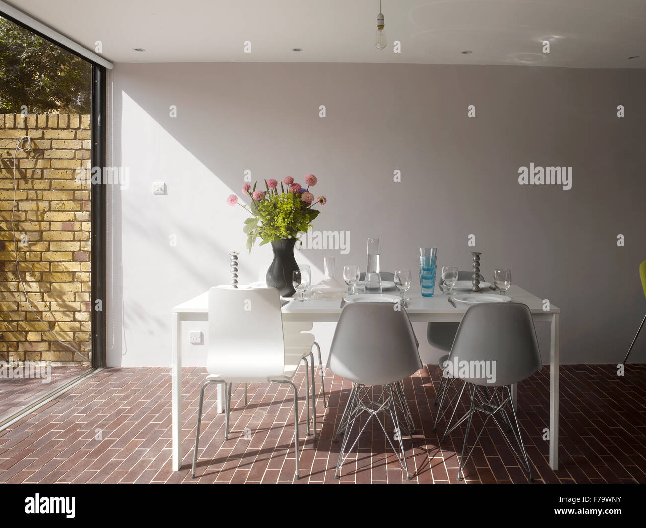Dining Table  in refurbished 1960s social housing, Vauxhall, London, England, UK - Stock Image