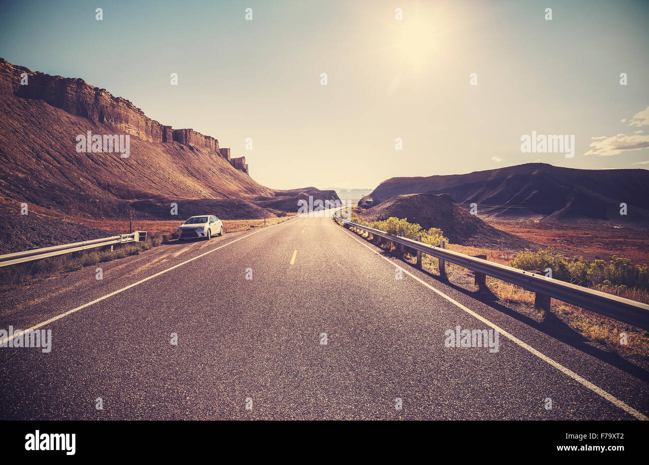 Retro toned desert highway against sun, travel concept. - Stock Image