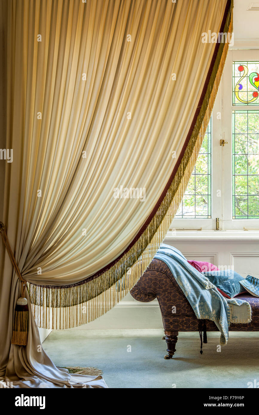 Gold draped curtain and chaise longue in the master bedroom of designer Erica Pols. Window treatment. - Stock Image
