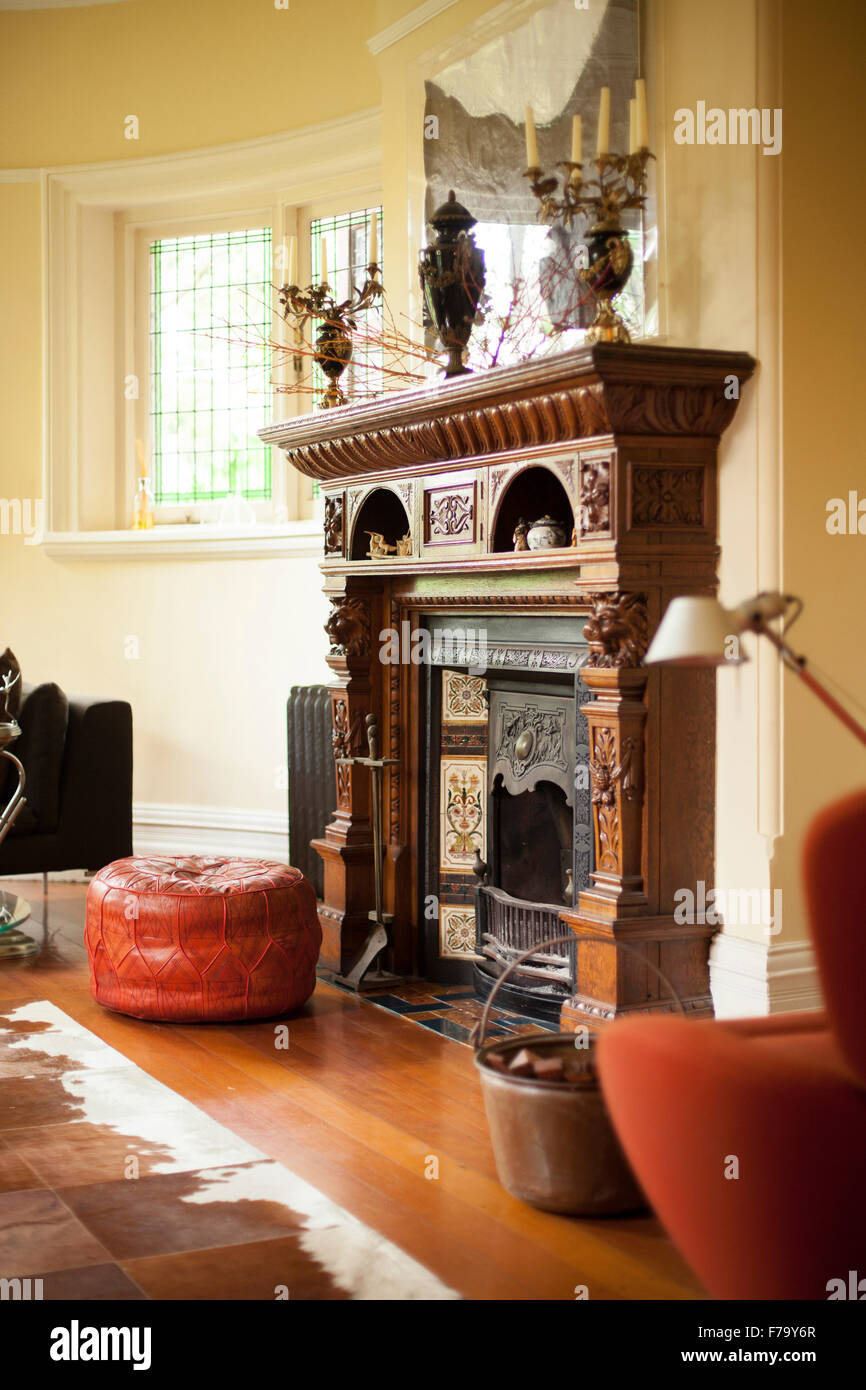Leather pouf and seat in Moroccan style by a carved wooden fireplace in a living room with a wooden floor an an - Stock Image