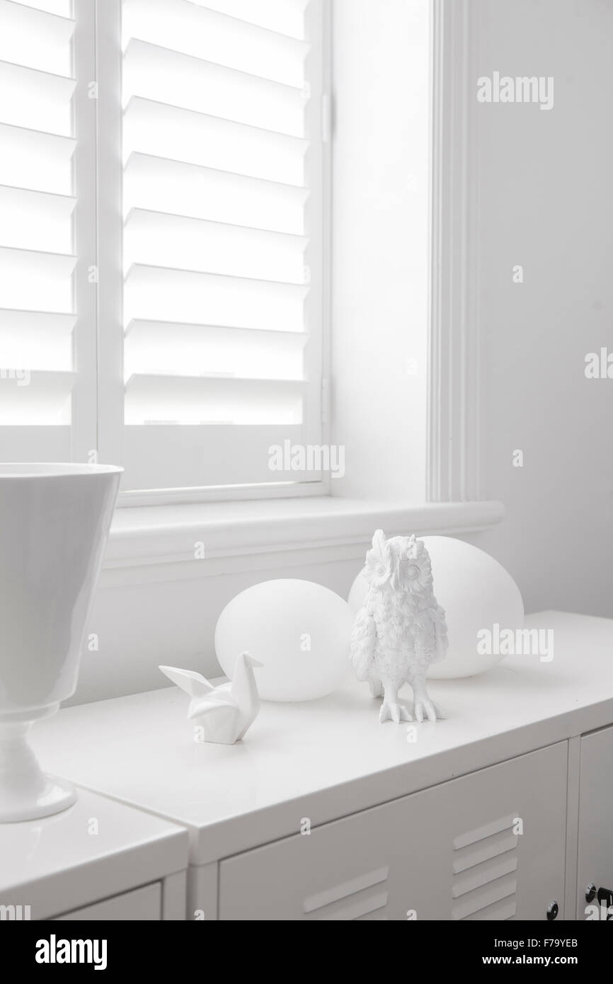 White ornaments and shutters at window in Sydney home of designer ...