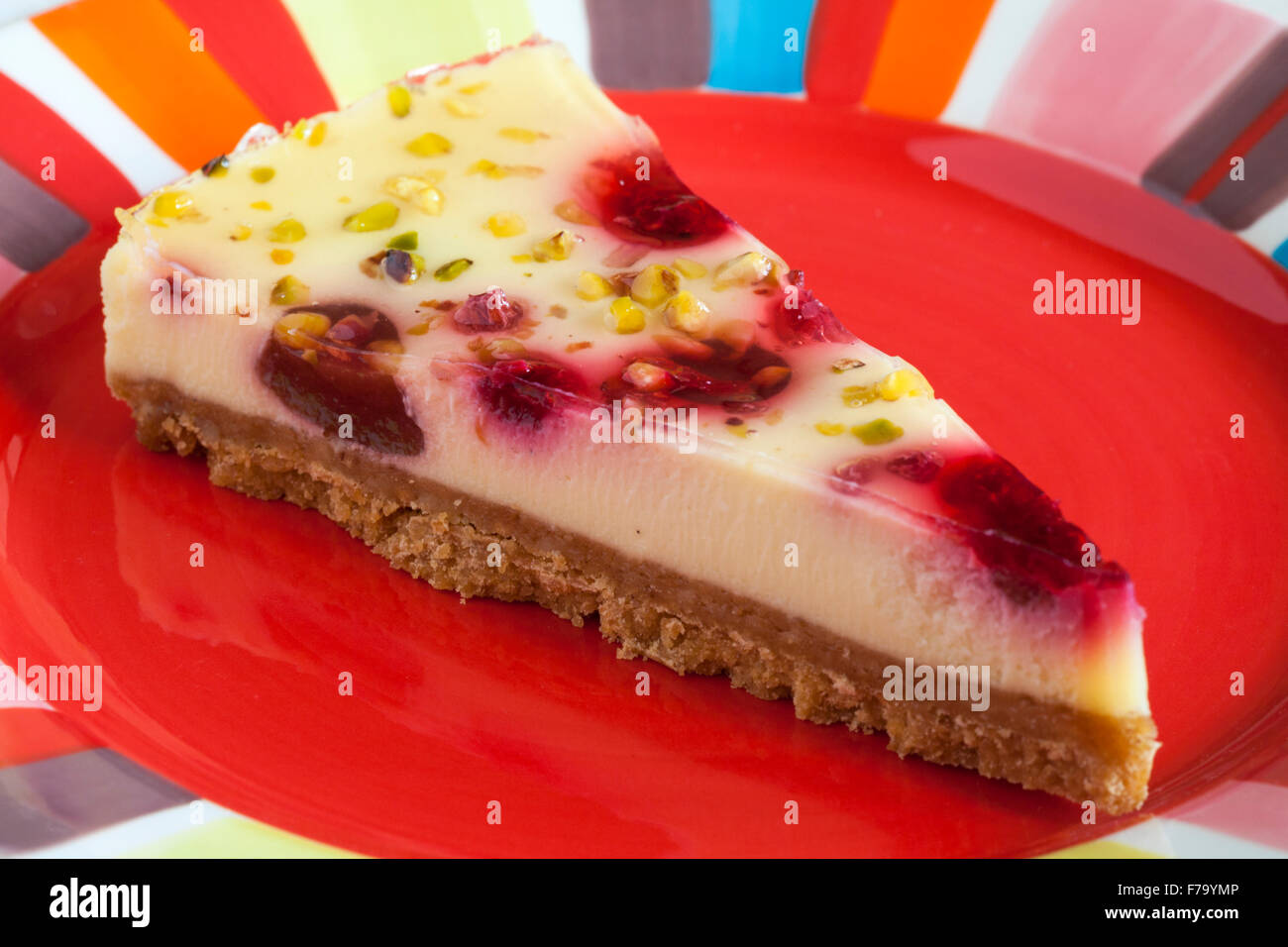 Tesco finest Raspberry & Pistachio cheesecake slice on red colourful plate - Stock Image