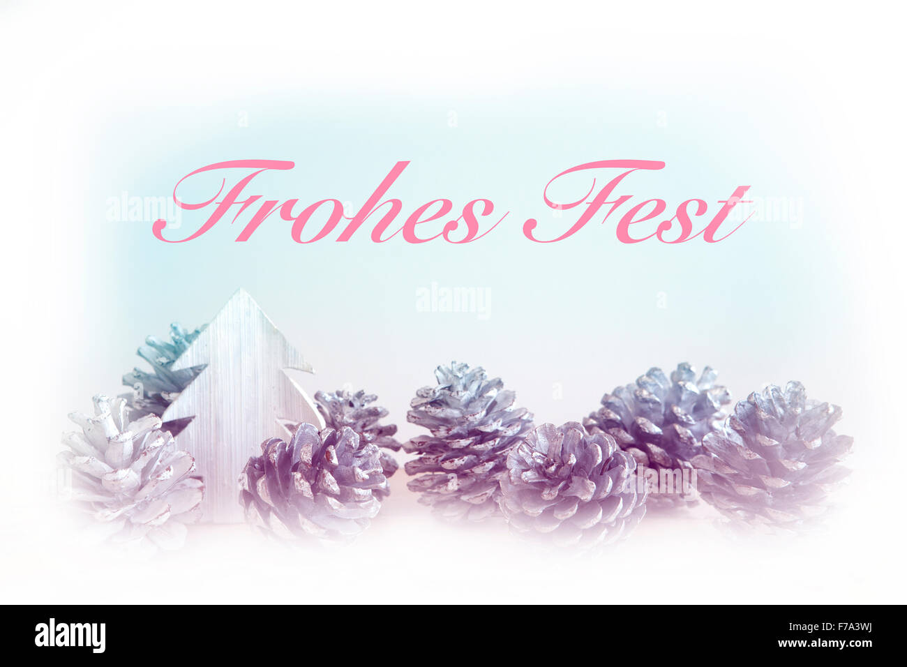 german 'Frohes Fest' (Merry Christmas) with pinecones and toy tree - Stock Image
