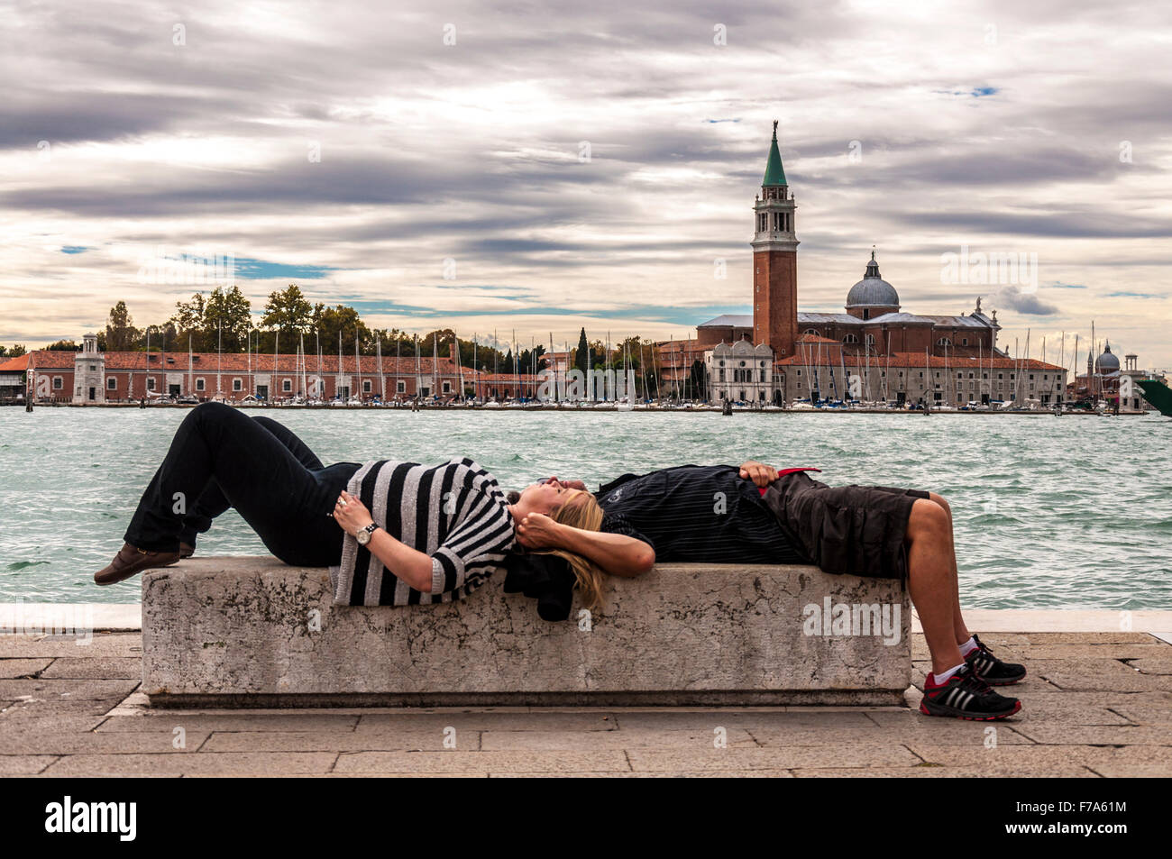 Tourist couple asleep or rest on a bench in Venice, Italy - Stock Image