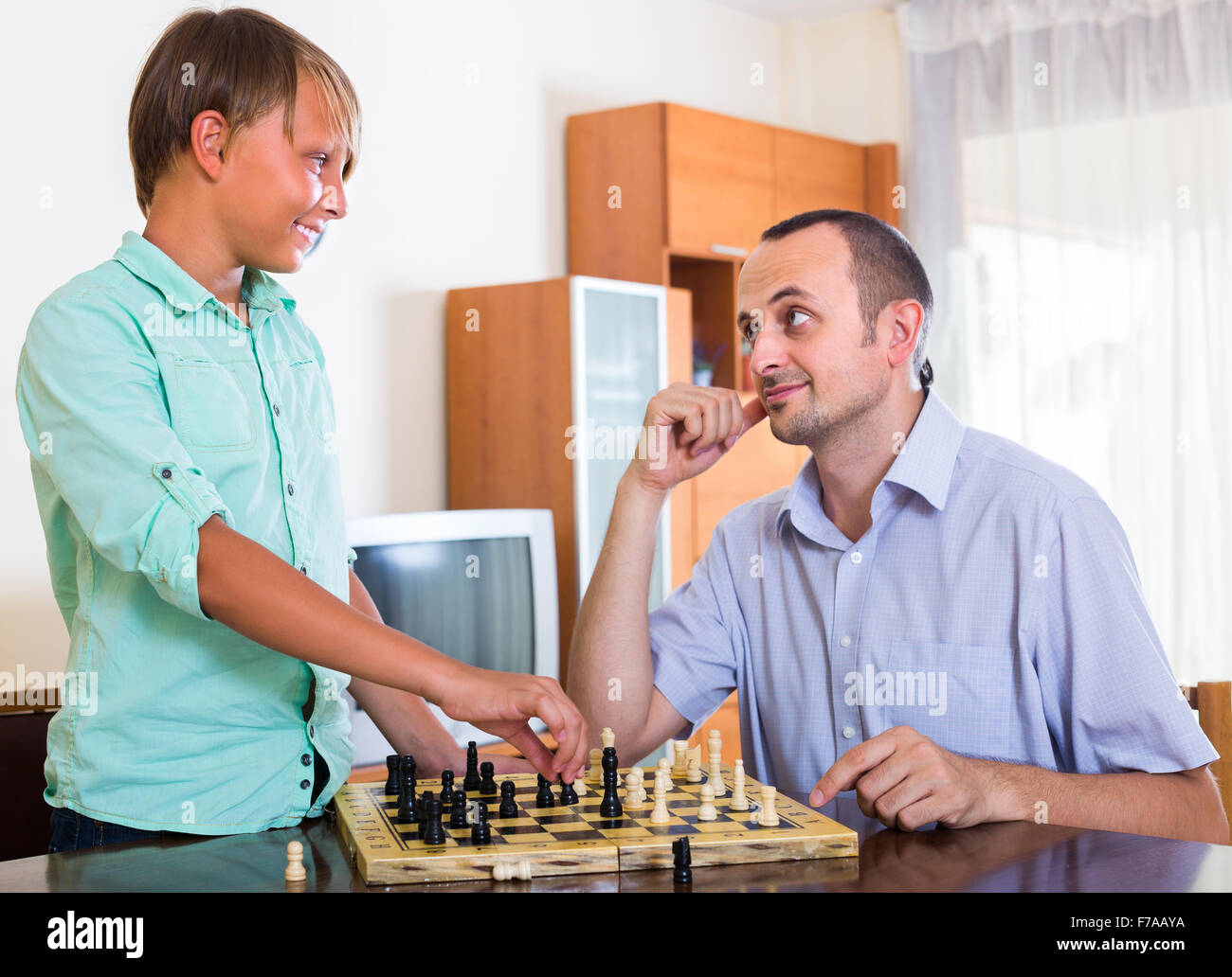 smiling adult man and cheerful teenager boy playing chess at home rh alamy com chest at home exercise chest at home workout