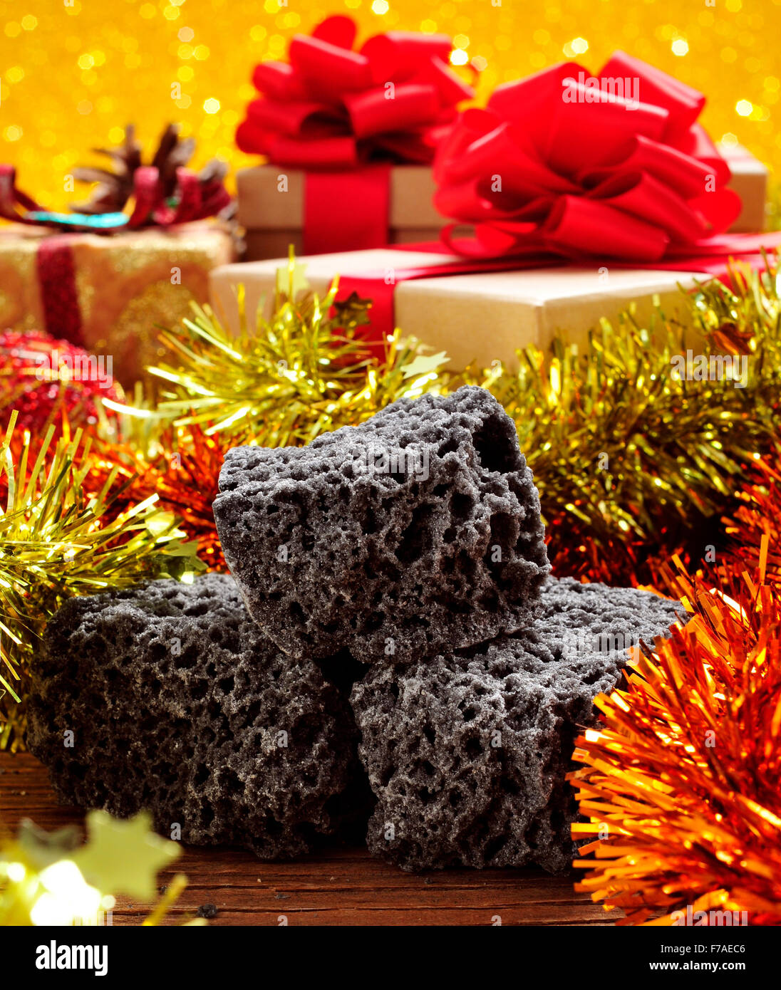 closeup of some lumps of candy coal and some christmas ornaments and gifts - Stock Image
