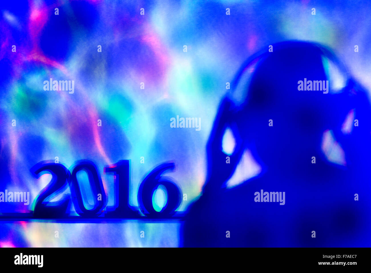 colorful lights projected on the number 2016, as the new year, and a disc jockey man wearing headphones in a dance - Stock Image