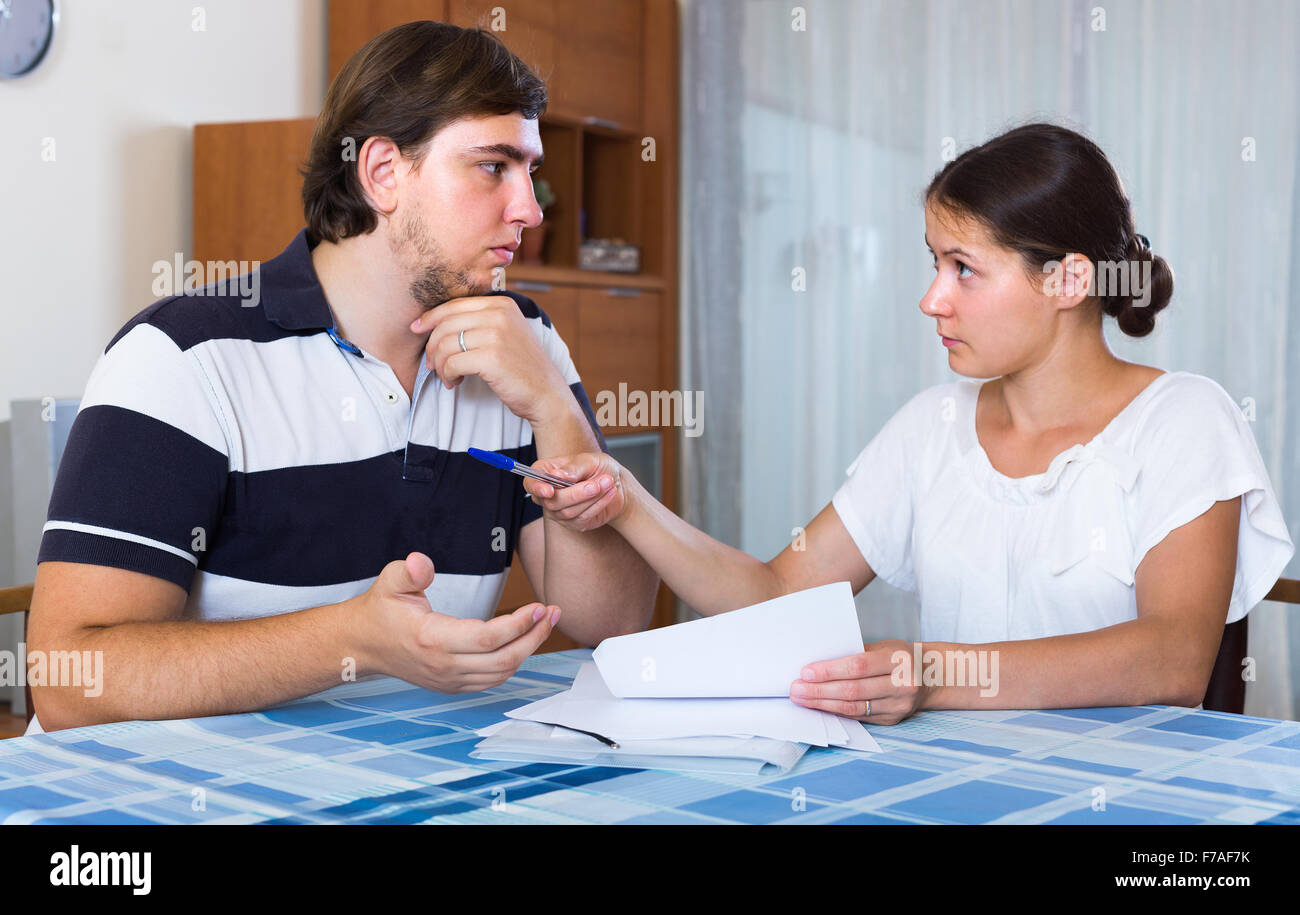 Married couple counting family budget sitting at desk with documents Stock Photo