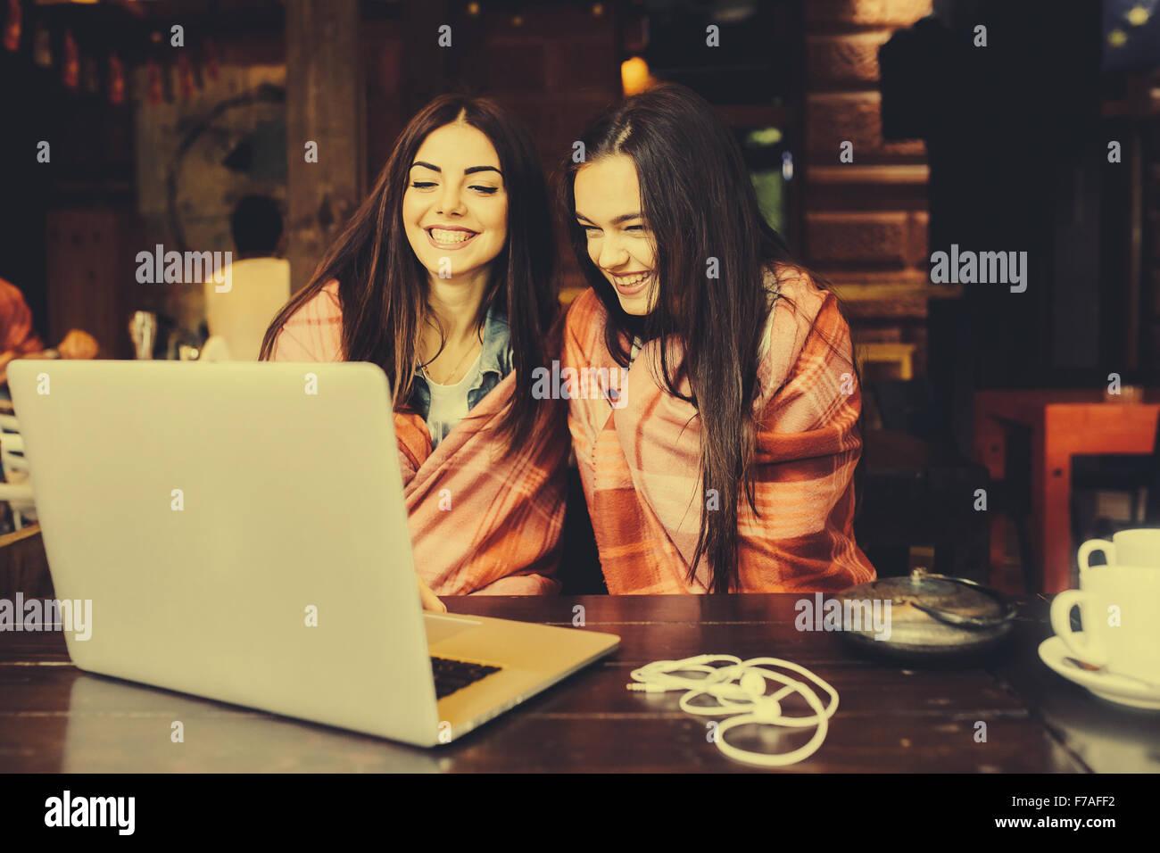 two girls watching something in laptop - Stock Image