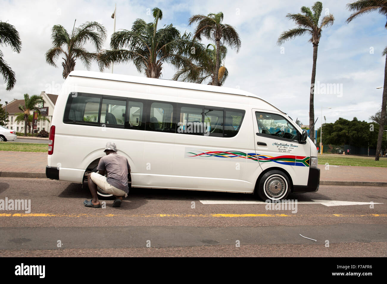 A taxi driver repairs his minibus taxi in the Warwick Triangle taxi stand in Durban South Africa - Stock Image