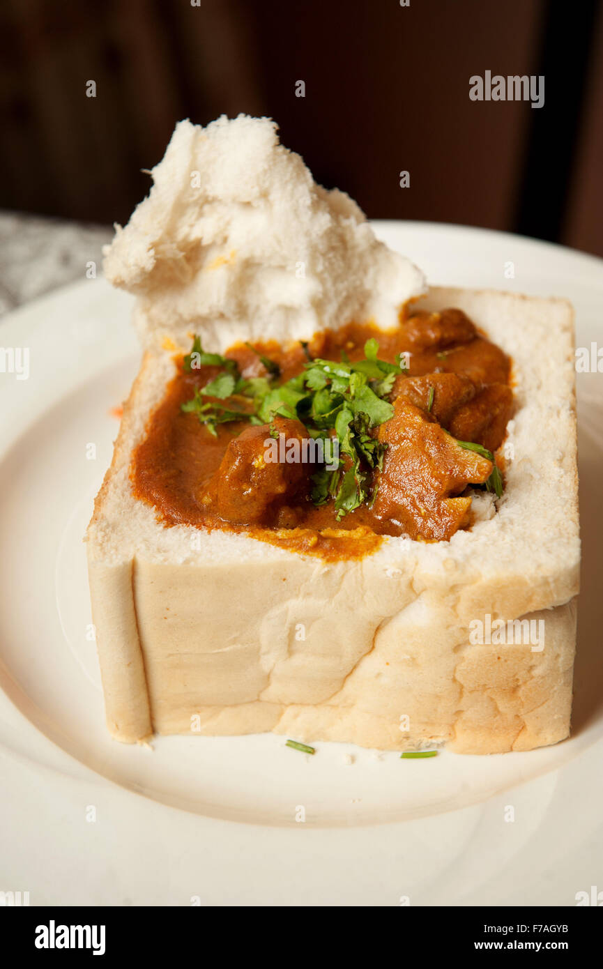 A traditional South African bunny chow, Indian curry served in a hollowed out loaf of bread.  Durban South Africa. - Stock Image