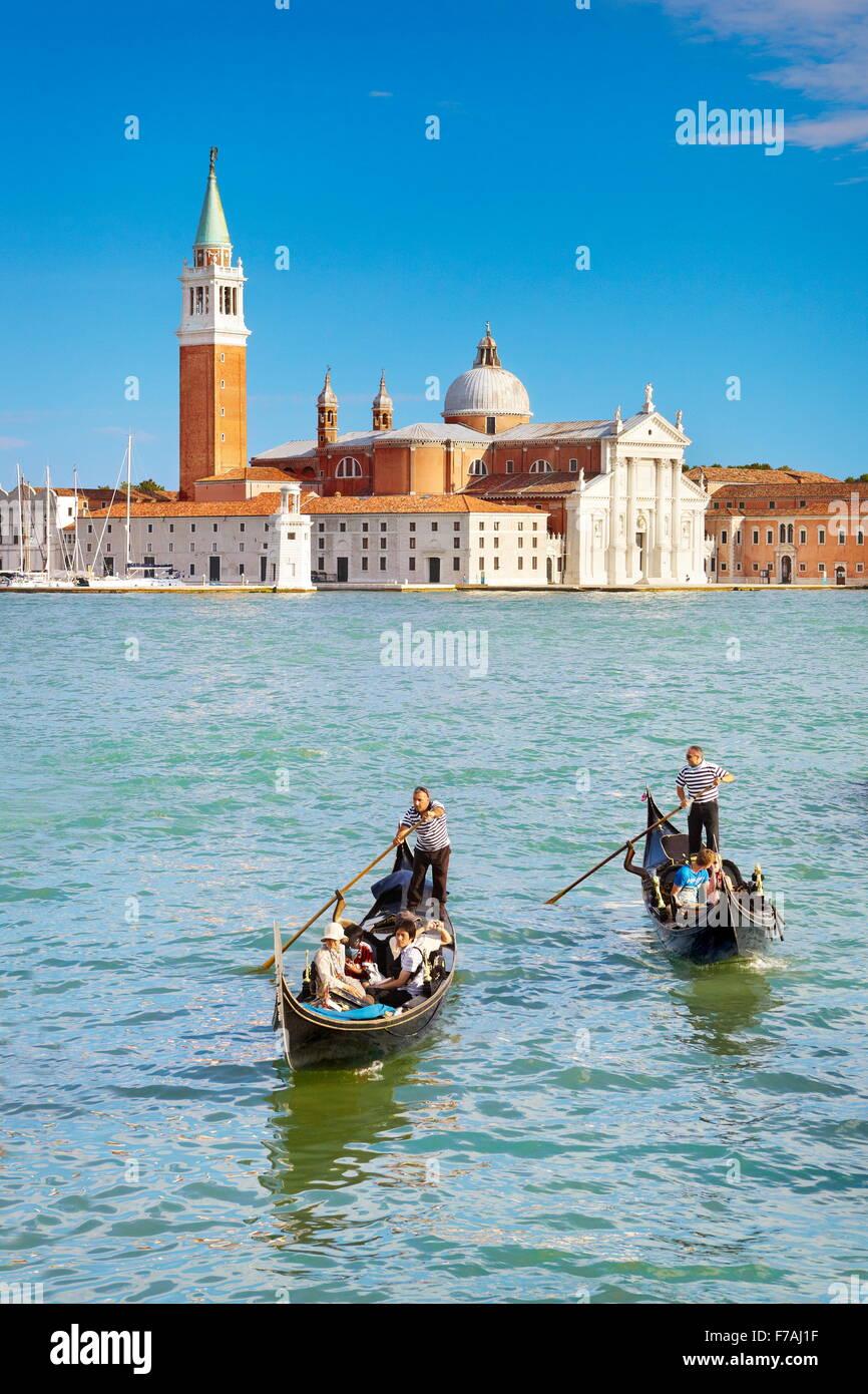 Tourists in venetian gondola on Grand Canal (Canal Grande) and San Giorgio Maggiore church in the background, Venice, - Stock Image