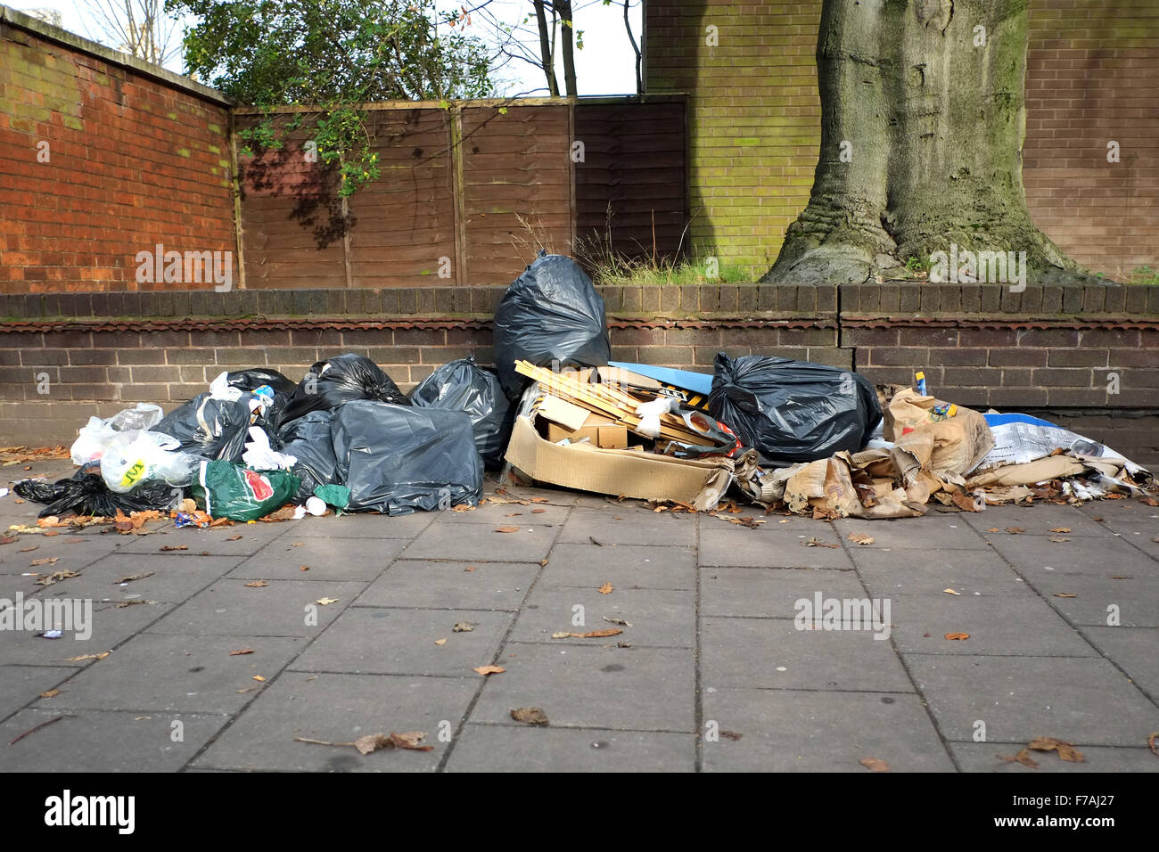 Refuse and rubbish left on a UK city center street. The rubbish, in bin bags and discarded boxes, is an eyesore - Stock Image
