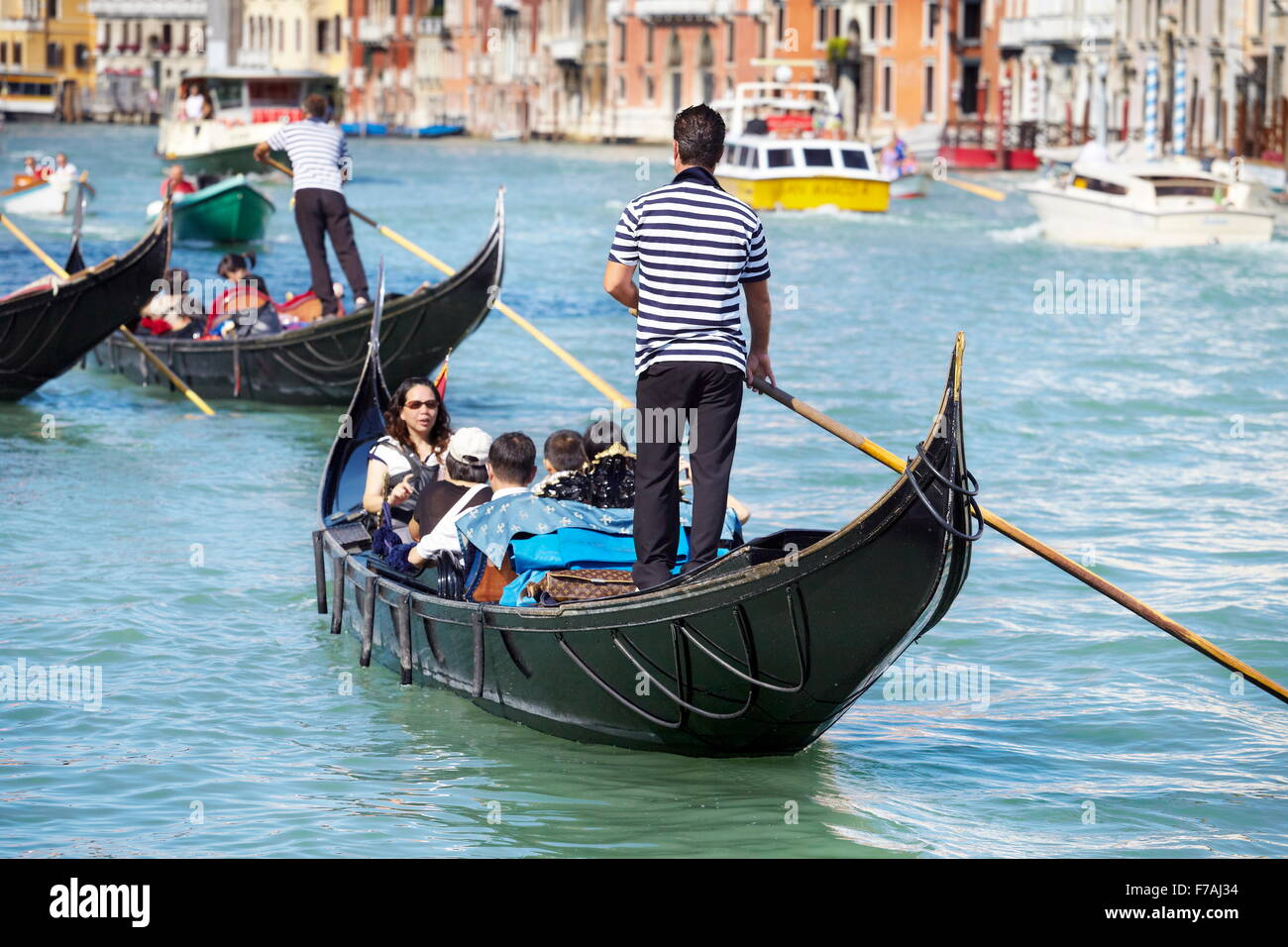Venetian Grand Canal (Canal Grande) - tourists in gondola exploring Venice, Italy - Stock Image