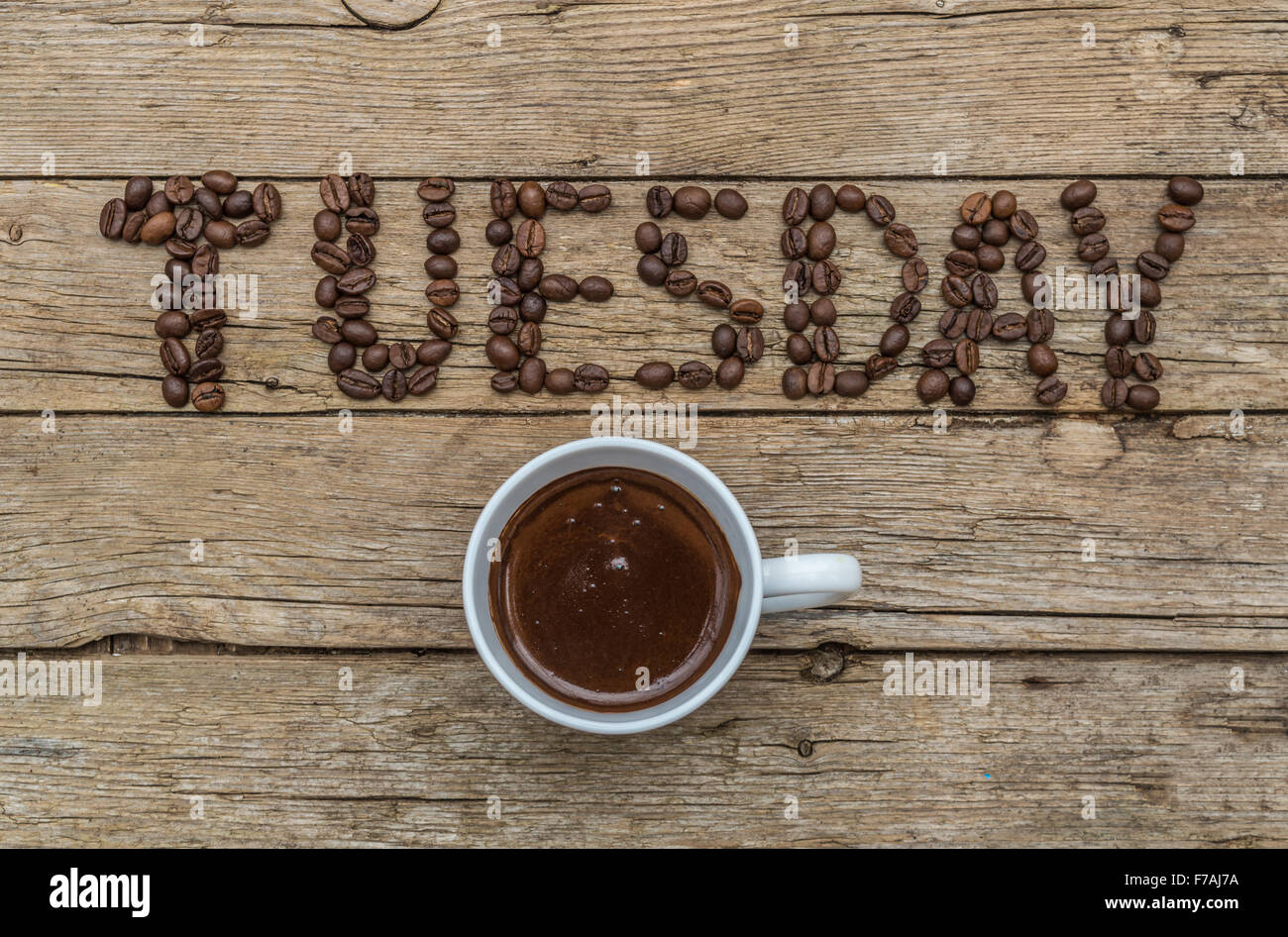 Cup of coffee on wooden background and TUESDAY coffee beans Stock Photo