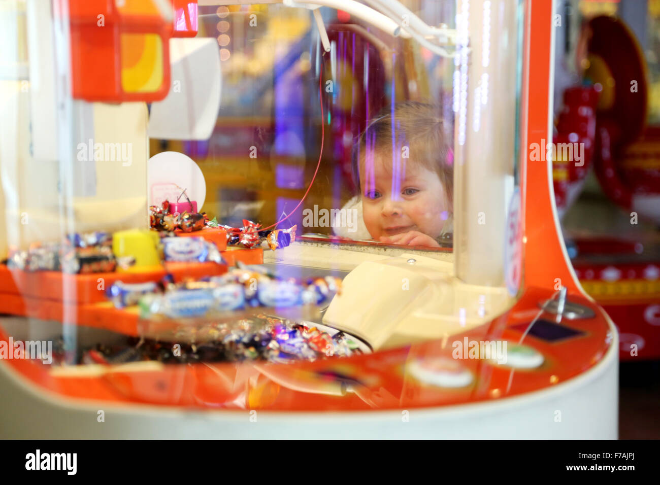 A young child looking into a grab machine in a traditional English amusement arcade. the machine offers sweets and - Stock Image