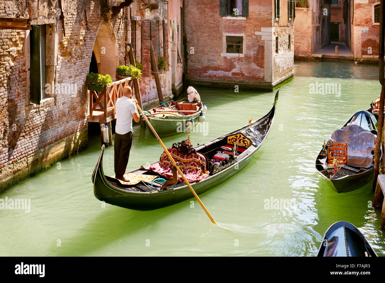 Gondolier in his gondola on venetian canal, Venice, Veneto, Italy, UNESCO - Stock Image