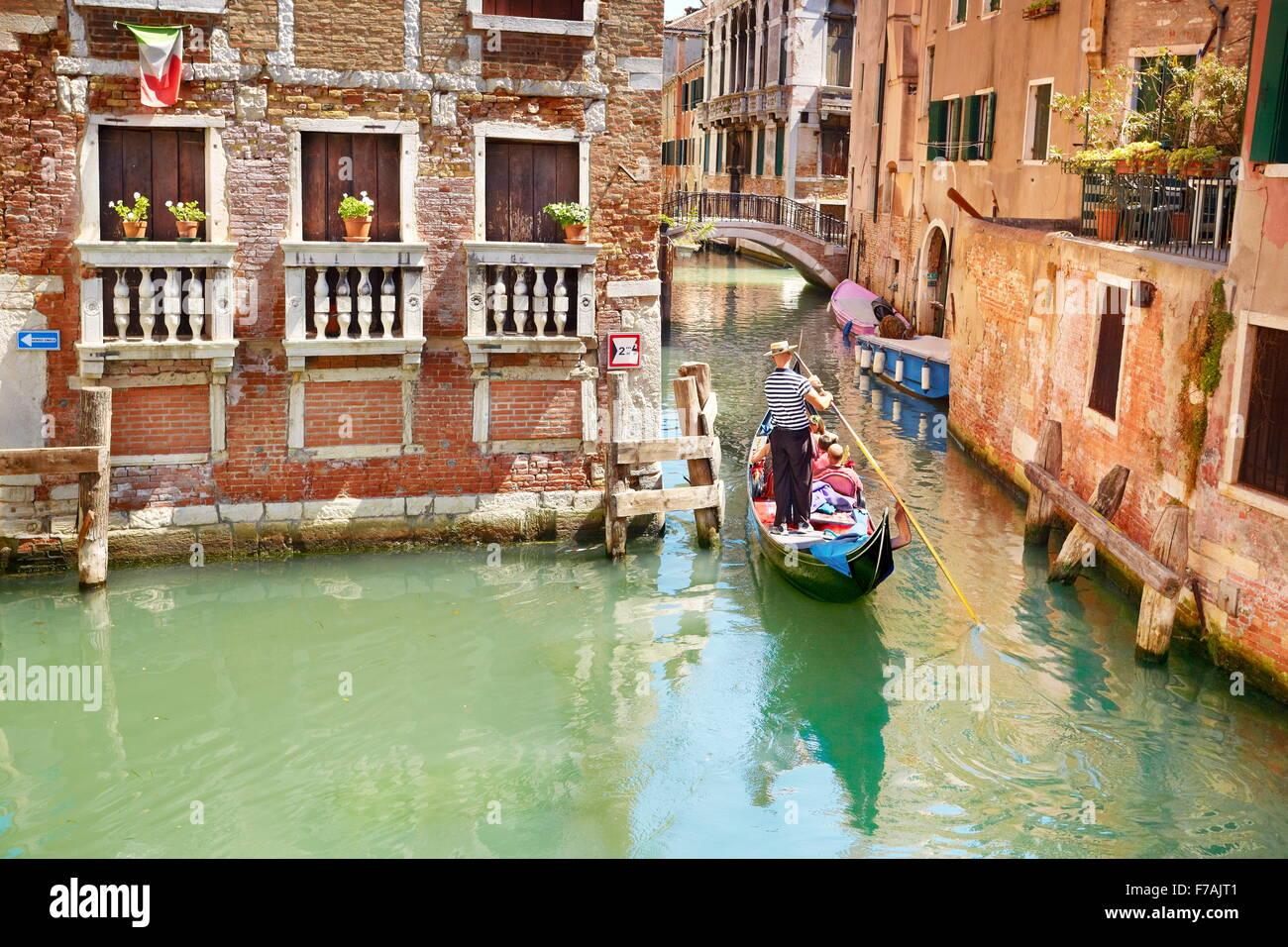 Tourists in gondola exploring venetian canal, Venice, Veneto, Italy, UNESCO - Stock Image