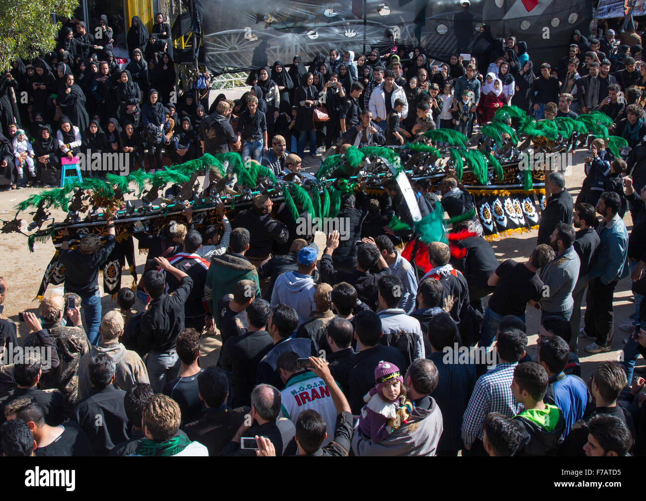 An Iranian Man Carries An Alam Is Helped By Shiite Mourners To Bow In Front Of A Mosque On Ashura, The Day Of The - Stock Image