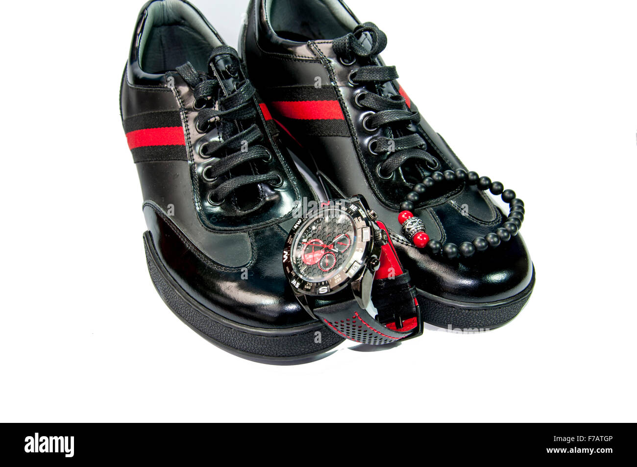 Black men shoes with red stripe, watch and bracelet isolated by white background - Stock Image