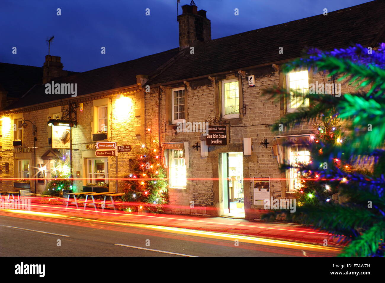 Christmas trees and light trails illuminate the main street in Castleton, a pretty village in Derbyshire's Peak Stock Photo