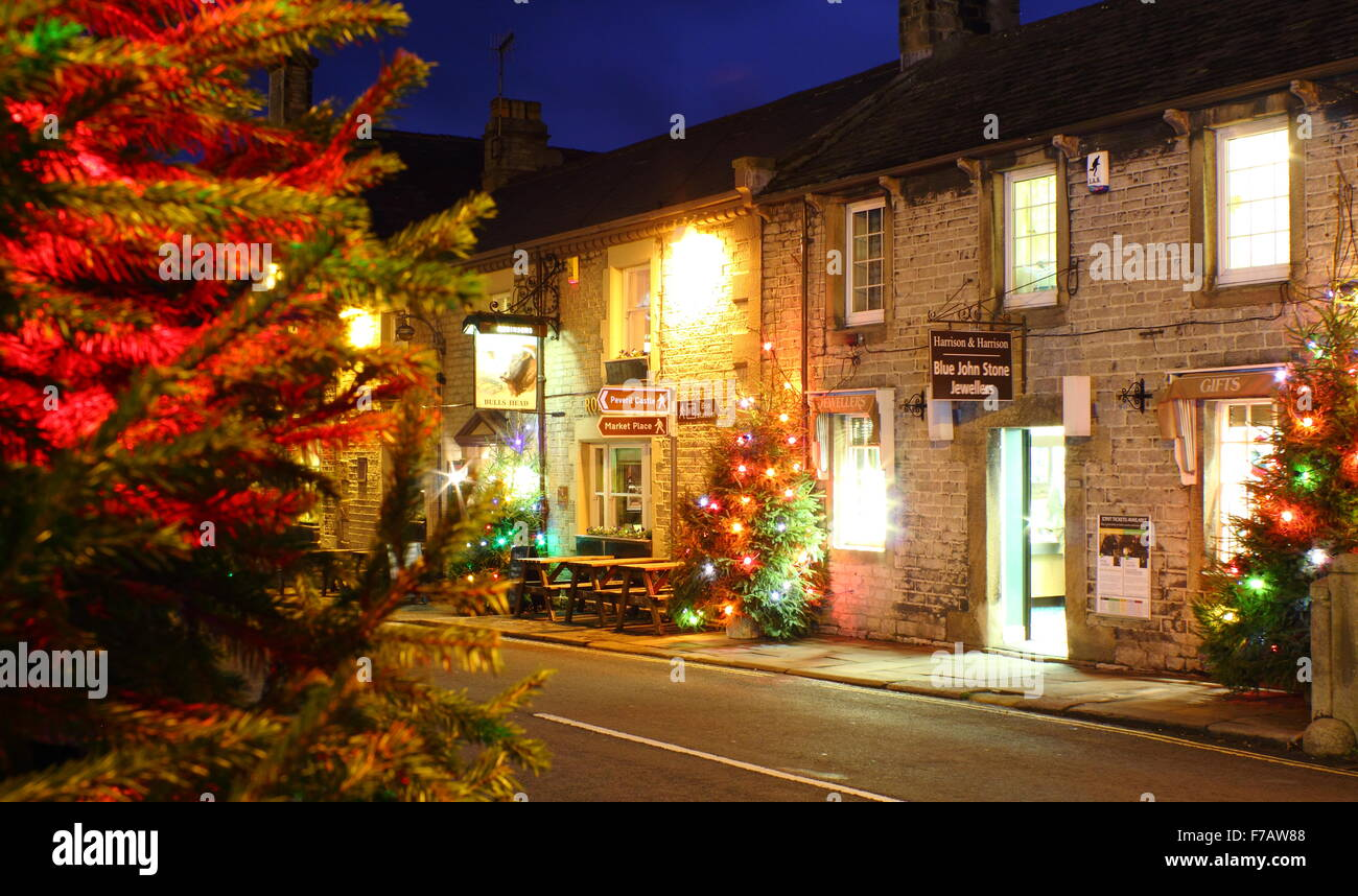 Christmas trees strung with fairy lights line the main street in Castleton, a pretty village in Derbyshire's Peak Stock Photo