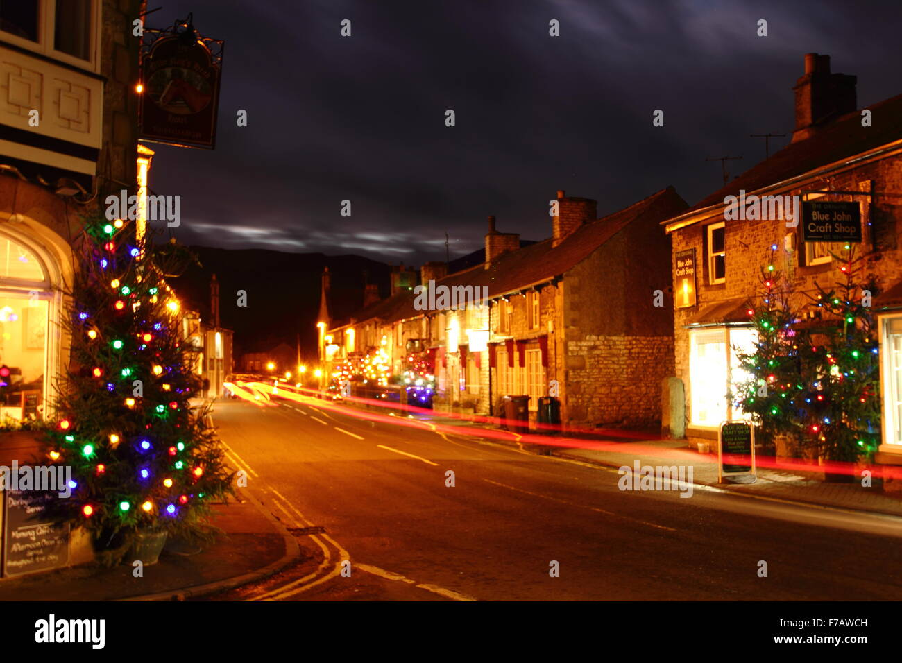 Christmas trees hung with fairy lights, illuminate the main street in Castleton, a village in the Hope Valley, Peak Stock Photo