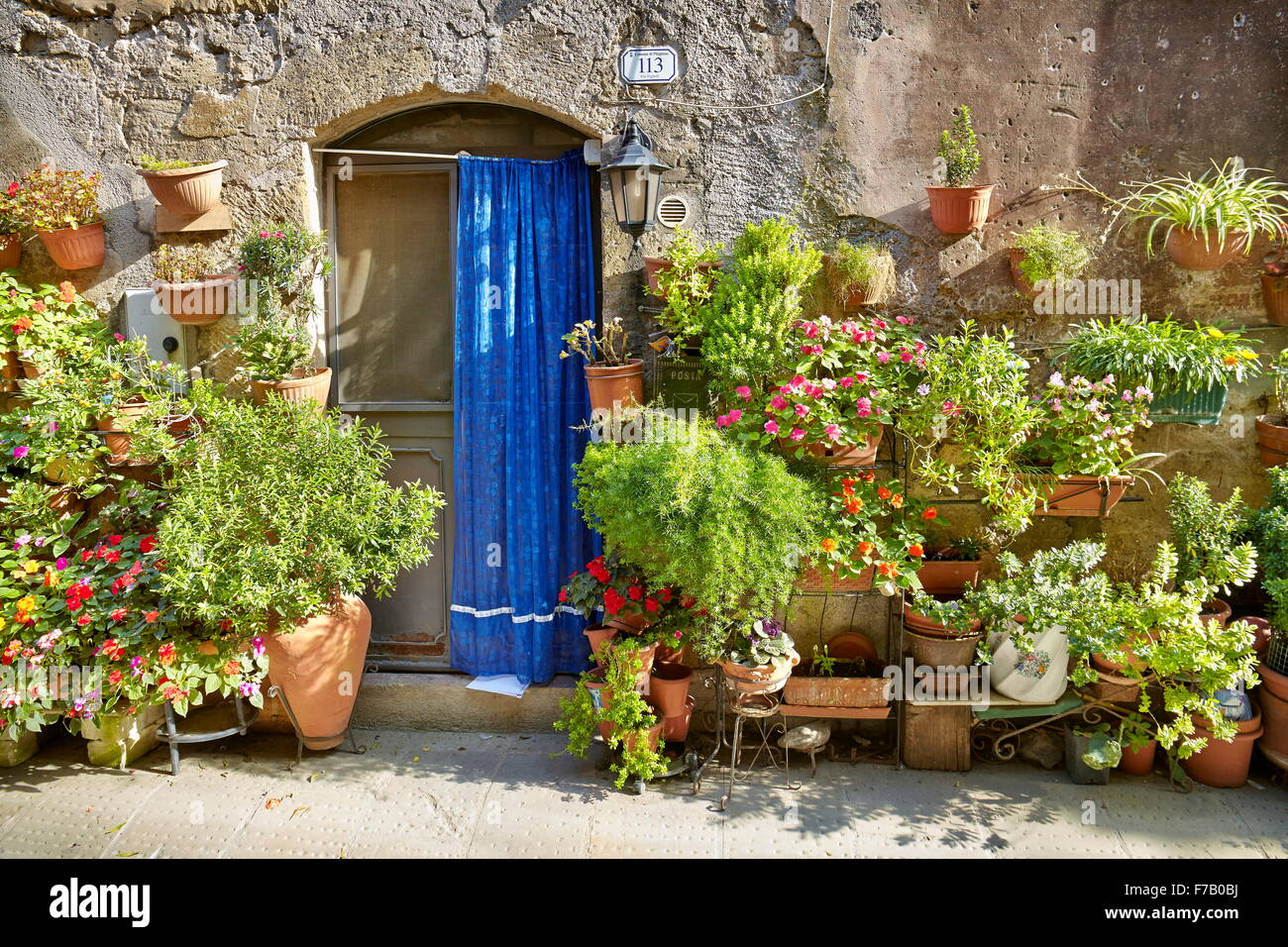 Entrance decorated with flowers, Pitigliano, Tuscany, Italy - Stock Image