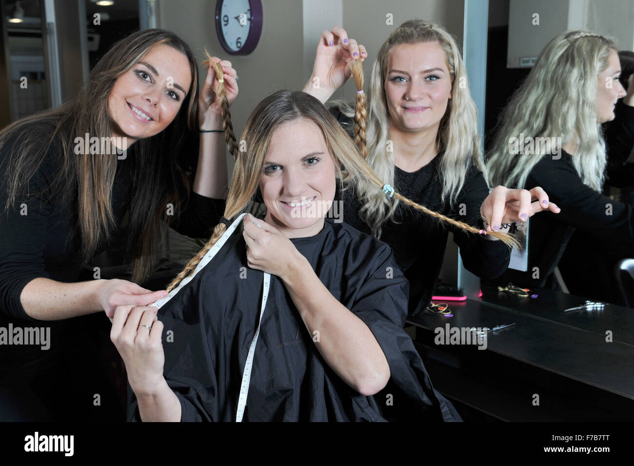 Young woman having her hair cut off for charity by hairdressers at