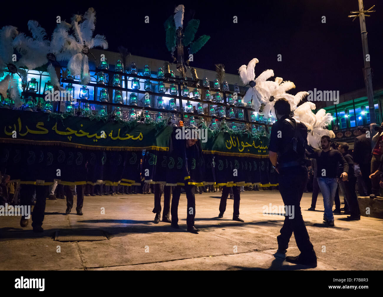 An Iranian Man Carries An Alam Is Helped By Shiite Muslim Mourners To Keep His Balance On Ashura, The Day Of The - Stock Image