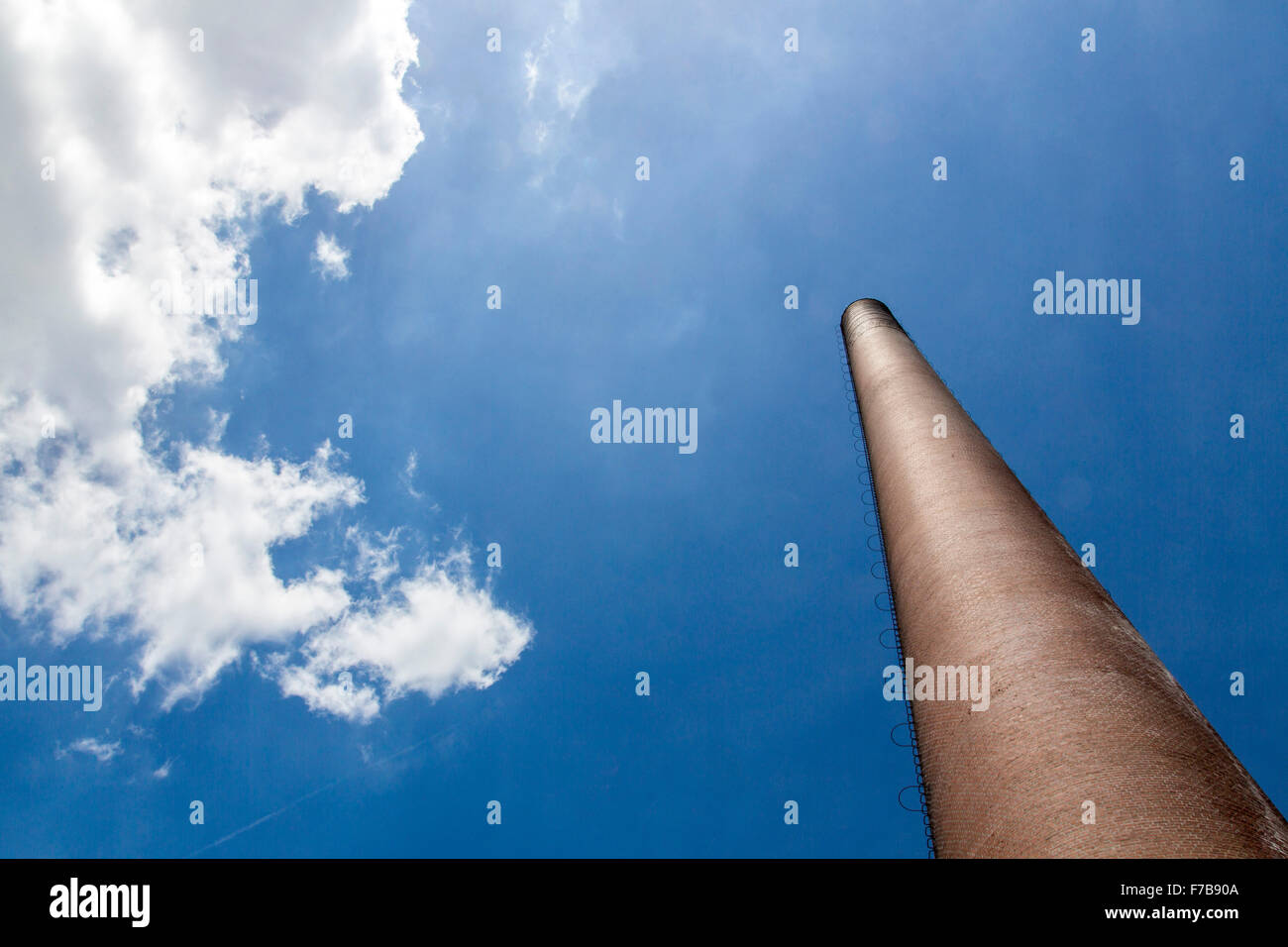 Industrial chimney, made of red bricks, blue sky, white cloud, - Stock Image