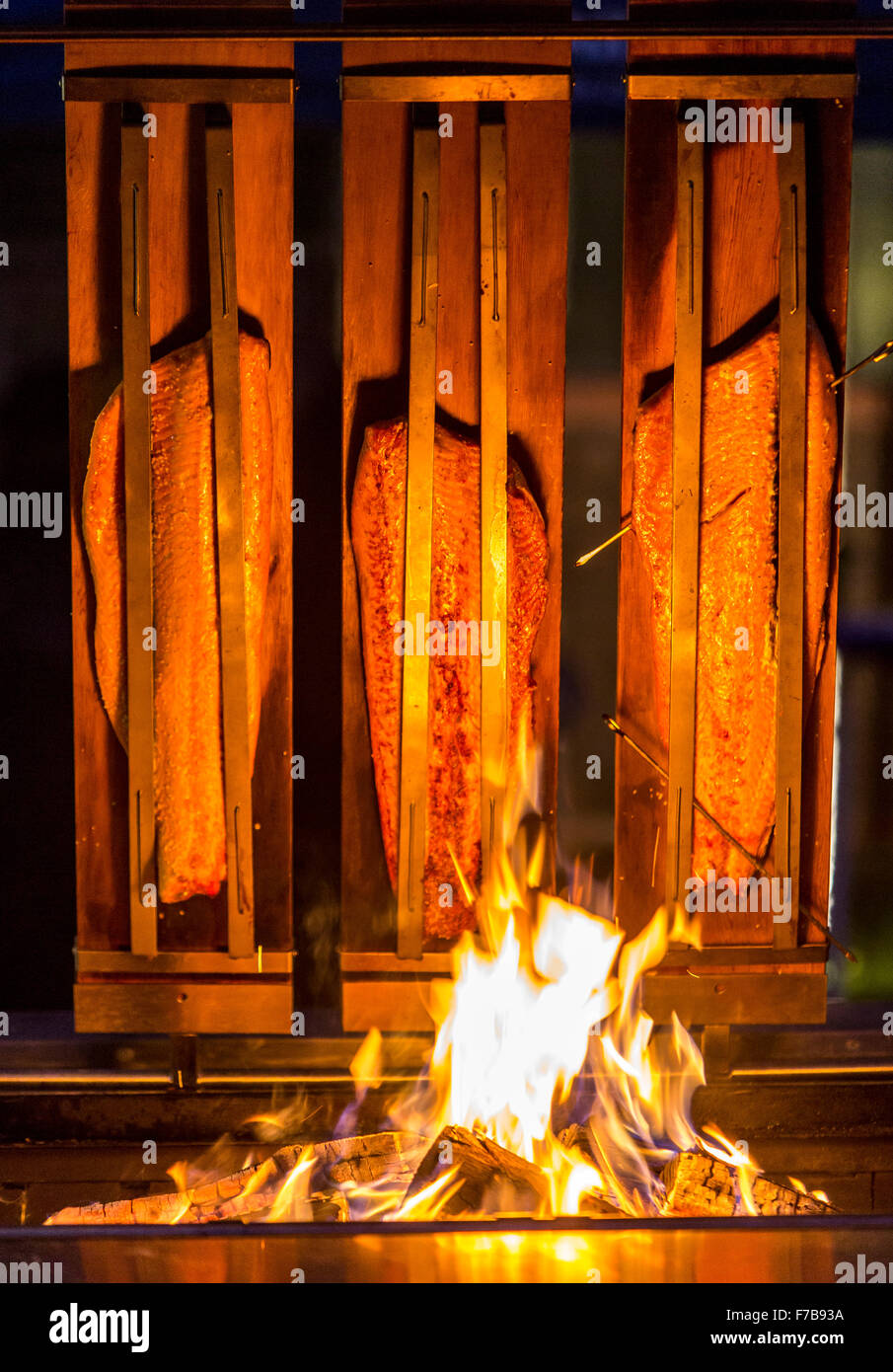 Salmon is smoked and grilled over open fire, specialty on a food market - Stock Image