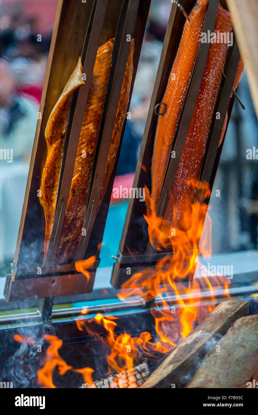 Salmon is smoked and grilled over open fire, specialty on a food market Stock Photo