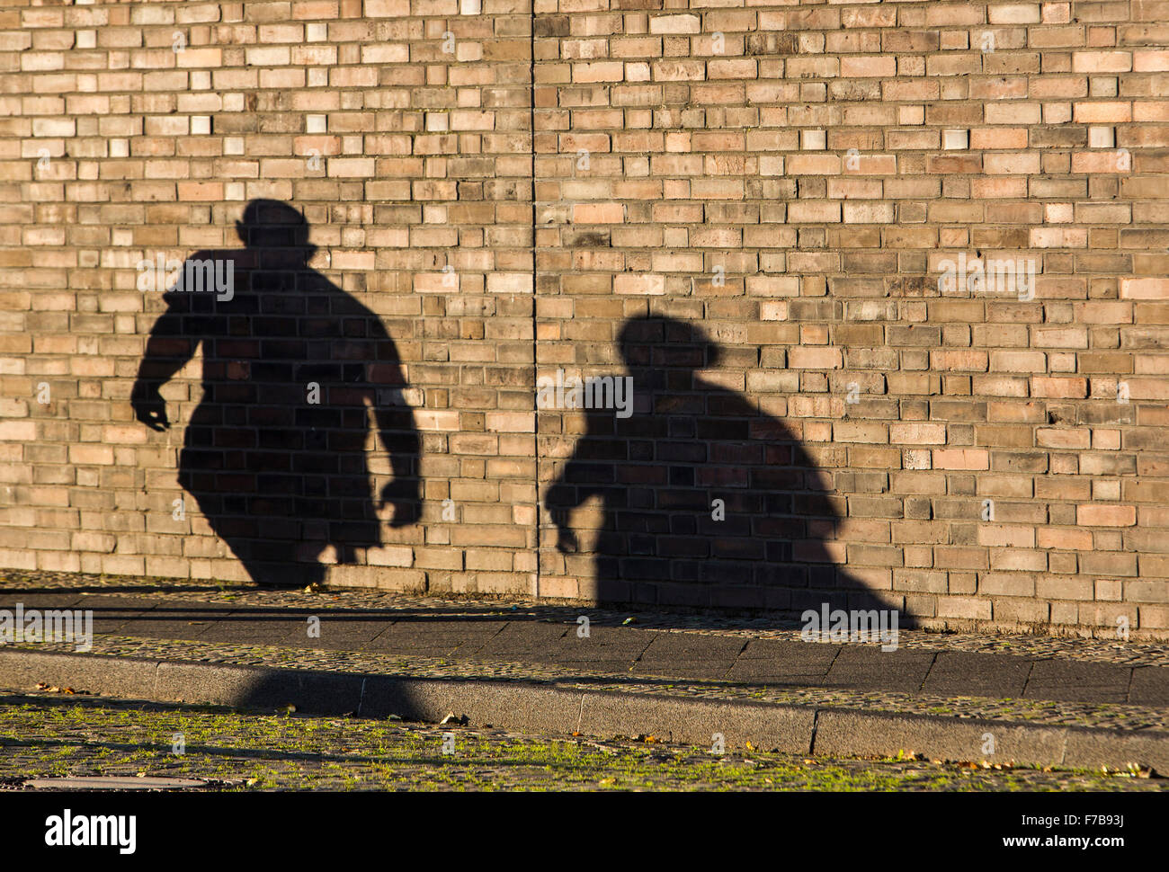 Shadow of 2 Persons, man, woman, on a brick wall - Stock Image