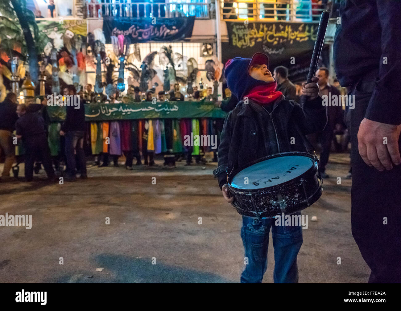 Boy With A Drum Speaking To His Father In Front Of An Alam On Ashura, The Day Of The Death Of Imam Hussein, Golestan - Stock Image