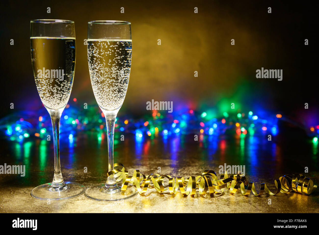 two glasses of champagne on a bright background with garlands Stock Photo