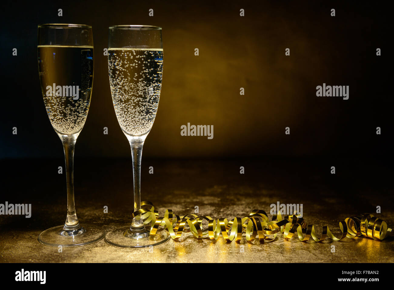 two glasses of champagne on a gold background. Christmas and New Year theme - Stock Image