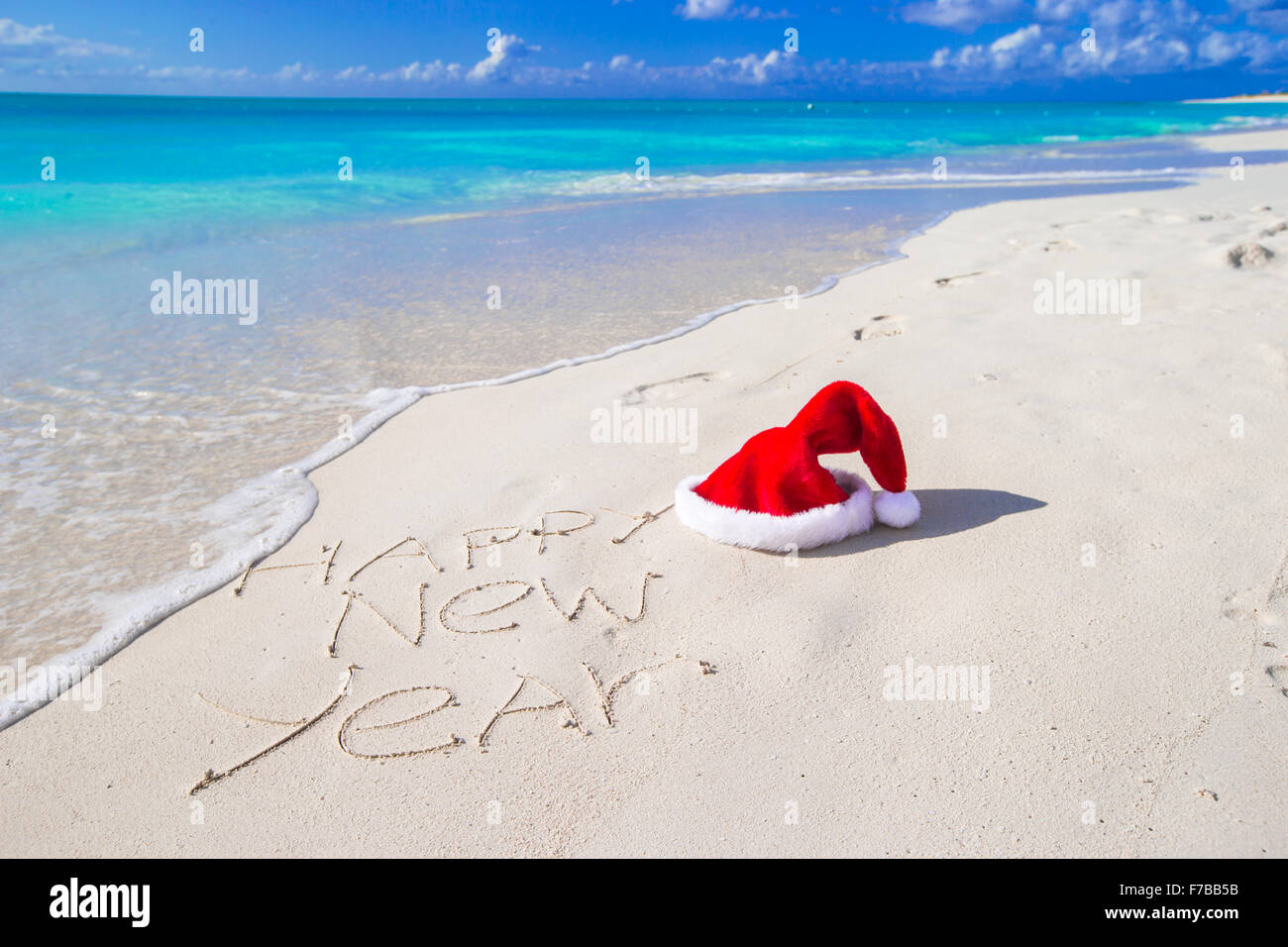 happy new year written on beach white sand with red santa hat