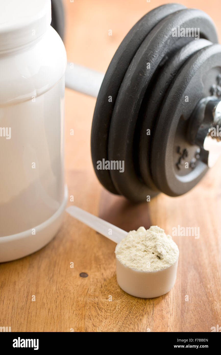 the whey protein in scoop and dumbbell - Stock Image