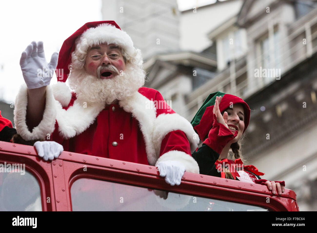 London, UK. 28 November 2015. Santa Claus travels with an elf on a double-decker bus. The inaugural Hamleys Christmas - Stock Image