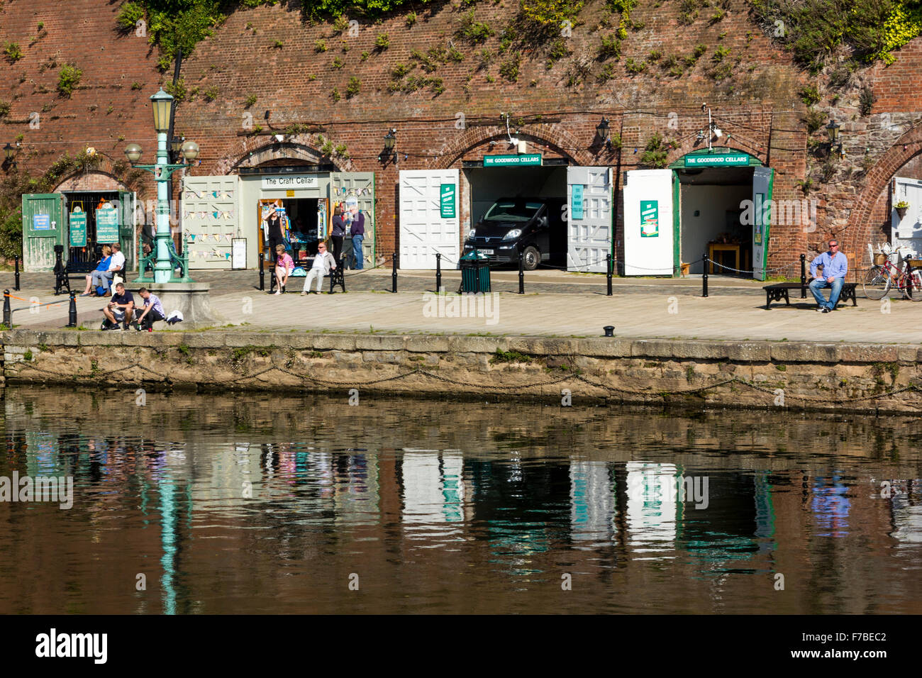 Shops at The Historic Old Cellars with River Exe Reflections and People, on a Sunny Autumn Afternoon, Exeter Quay, - Stock Image