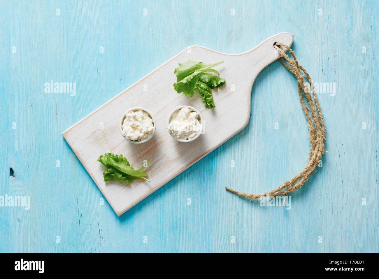 Cottage cheese in two white bowls on blue wooden table and salad - Stock Image