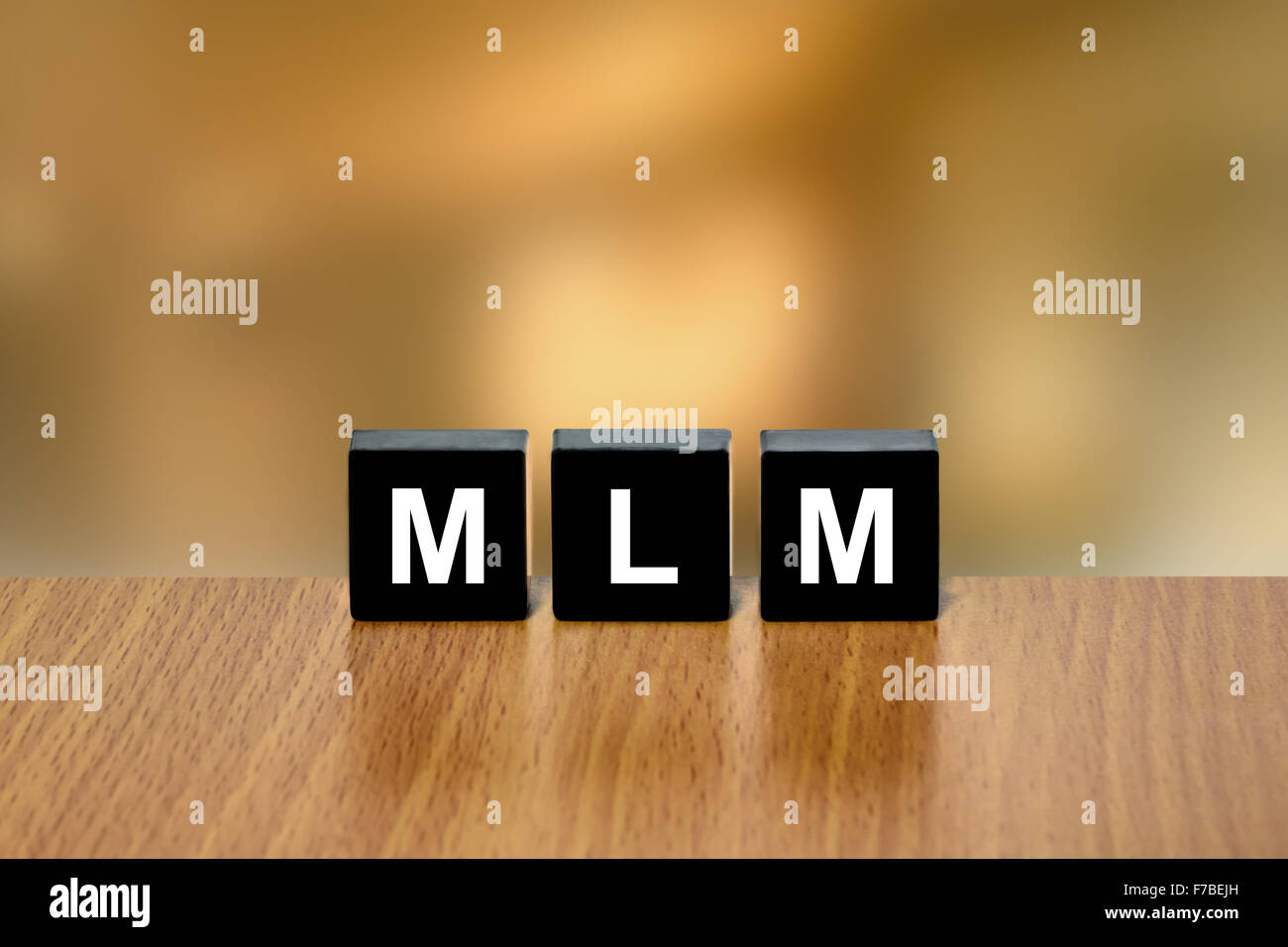 MLM or Multi Level Marketing on black block with blurred background Stock Photo