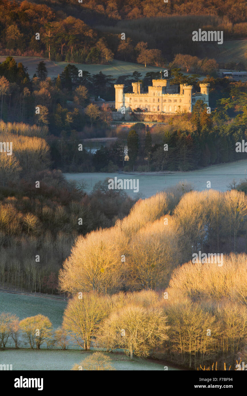 Eastnor Castle, Herefordshire is lit up by Sunrise. Frost on the bare trees makes them glow orange in the strong Stock Photo